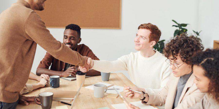 Mand giver håndtryk til kollega på arbejdet