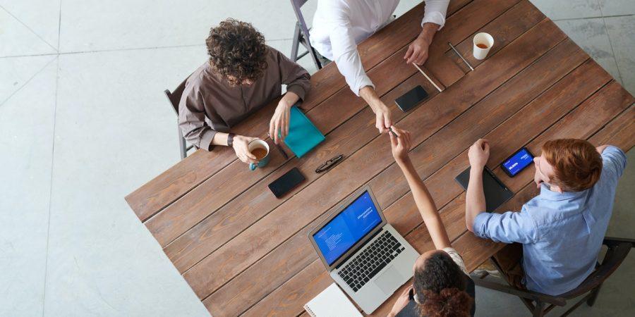 fire mennesker sidder rundt om et bord til møde