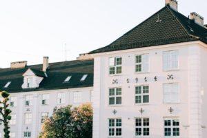 Hvidt hus med sort tag og 3 etager